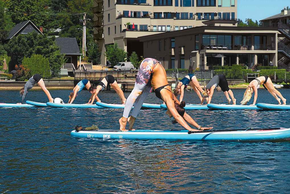 Hold steady! PaddleFlow Yoga at Juanita Beach Park in Kirkland on Wednesdays at noon combines yoga, Pilates and stand-up paddleboarding. (Courtesy of Northwest Paddle Surfers)