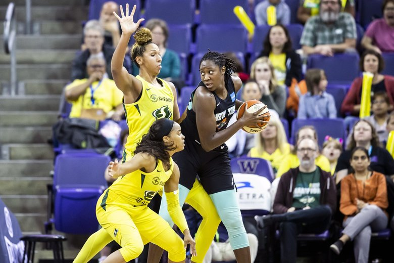 Seattle Storm guard Jordin Canada, bottom, and center Mercedes Russell defend New York Liberty center Tina Charles in the second half as the Seattle Storm take on the New York Liberty at Alaska Airlines Arena at the University of Washington Wednesday July 3, 2019. Charles was the leading scorer in the game with 26 points. (Bettina Hansen / The Seattle Times)