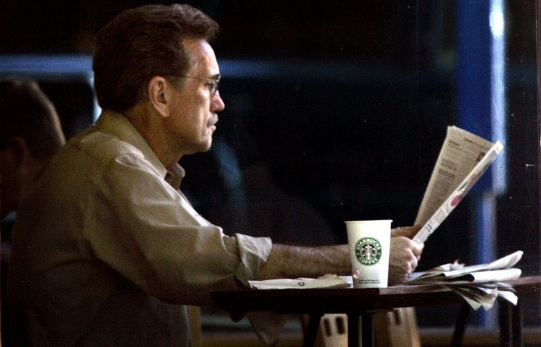 Jim Johnson reads a newspaper with his morning cup of coffee at a Starbucks in downtown Portland, Ore., Wednesday, May 3, 2006. Starbucks boosted its earnings targets for the year, saying it expects earnings will be 68 cents to 70 cents a share– 5 cents more than previously forecast. (AP Photo/Don Ryan)
