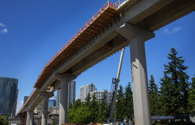A van at lower left  heads northbound on I-405  underneath the concrete girder bridge for light rail trains, with supplemental archwork in sections, between downtown Bellevue and the future Wilburton Station, looking westbound.  Shot Thursday, June 19, 2019. 210568