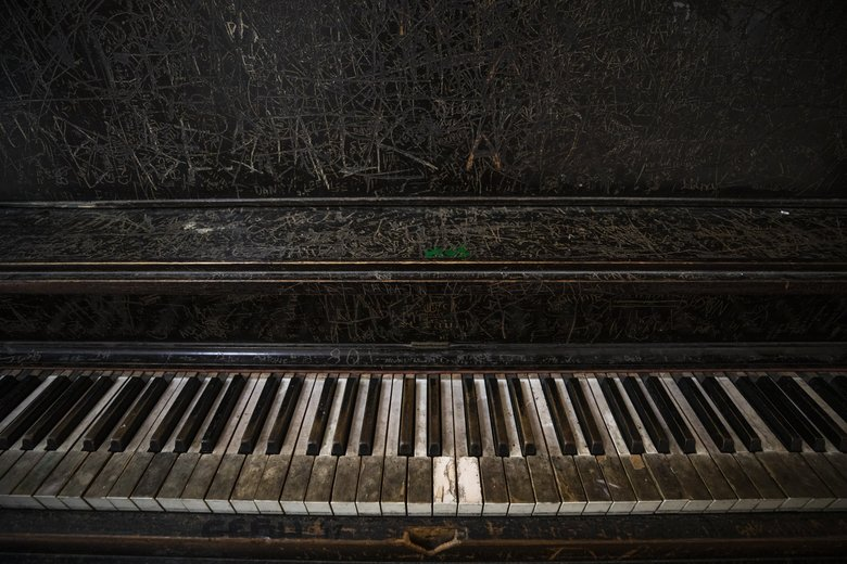 An old upright piano has become its own art project beyond the broken keys and out-of-tune sound over the decades at the Youngstown Cultural Arts Center. (Bettina Hansen / The Seattle Times)