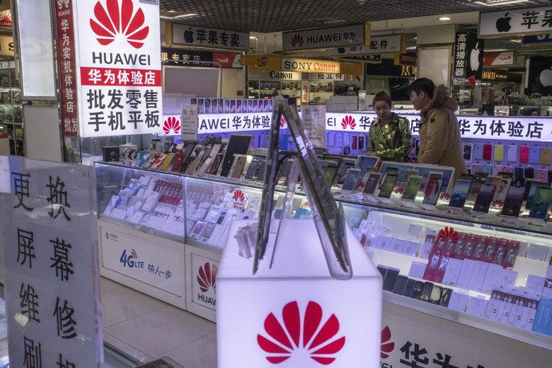 Customers browse a booth featuring Huawei products at a mall in Beijing in 2018.  (Gilles Sabrie / The New York Times)