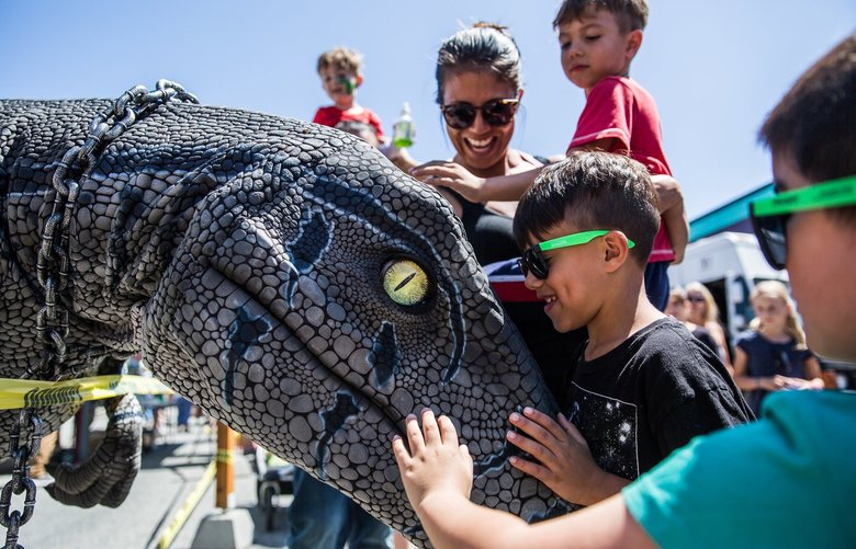 A very realistic looking raptor nudges Logal Wells at the Dino Crew booth at Kla Ha Ya days in Snohomish on Saturday afternoon, July 20. 210942 (Rebekah Welch / The Seattle Times)