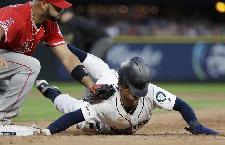 Seattle Mariners' Mallex Smith, right, loses his helmet as he is tagged out by Los Angeles Angels first baseman Albert Pujols at first base on a pick-off in the seventh inning of a baseball game Saturday, July 20, 2019, in Seattle. (AP Photo/Elaine Thompson) WAET112 WAET112