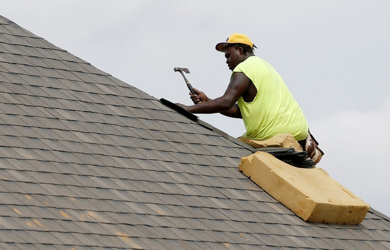 In this June 19, 2019, photo a worker balances on a steep roof as he lays down shingles on a roof on a new house in a Brandon, Miss., neighborhood. Government data on residential construction should provide insight into the state of the new home market. The Commerce Department is expected to report Wednesday, July 17, that builders broke ground on new apartments and single family homes in June at the slowest pace since February (AP Photo/Rogelio V. Solis) NYBZ136 NYBZ136