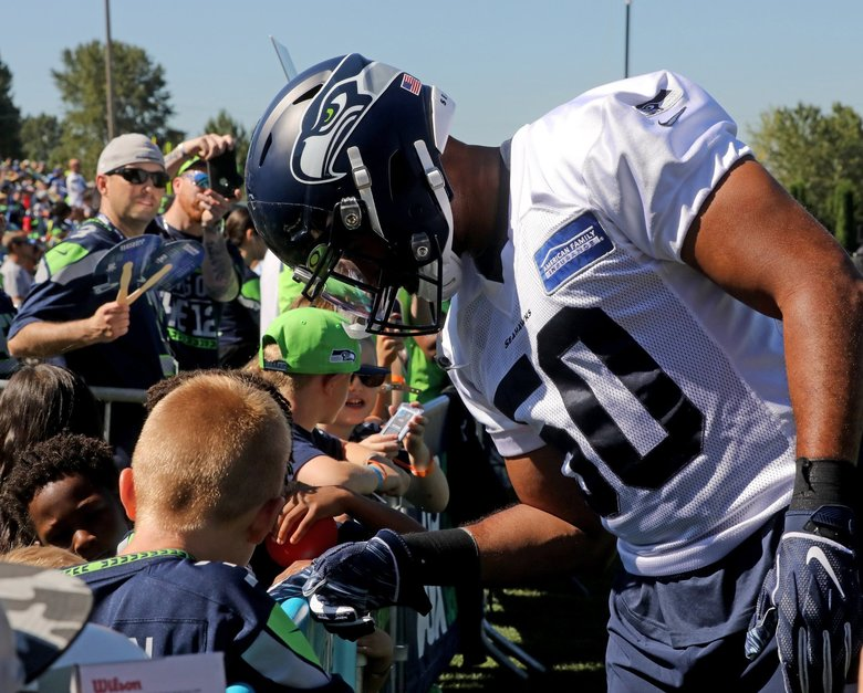 Seahawks linebacker K. J. Wright steps off the field to chat with fans at training camp at VMAC in Redmond on July 26, 2019. (Greg Gilbert / The Seattle Times)