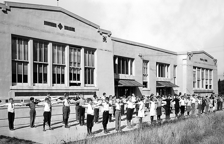 "THEN: In 1925, more than 60 students at then-11-year-old East Seattle School, some in dresses, ties or knickerbockers, take their exercise outside the school's east-facing backside. For a complete history of the school and its environs, see the 2013 book ""Mercer Island: From Haunted Wilderness to Coveted Community"" by Jane Meyer Brahm."