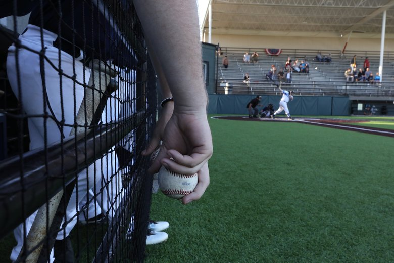 The baseball is a magnet for Highline Bears to pick up and handle during a game, hanging out in their dugout at Mel Olson Stadium, close to the action. A hitter for the opponent, the Laces Baseball Academy, swings and misses. (Alan Berner / The Seattle Times)