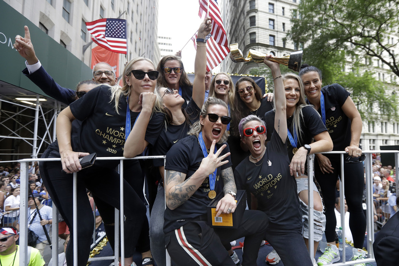 Megan Rapinoe holds the Women's World Cup trophy as the U.S. women's soccer team is celebrated with a parade along the Canyon of Heroes, Wednesday, July 10, 2019, in New York. The U.S. national team beat the Netherlands 2-0 to capture a record fourth Women's World Cup title. Wednesday, July 10, 2019. (AP Photo/Richard Drew)