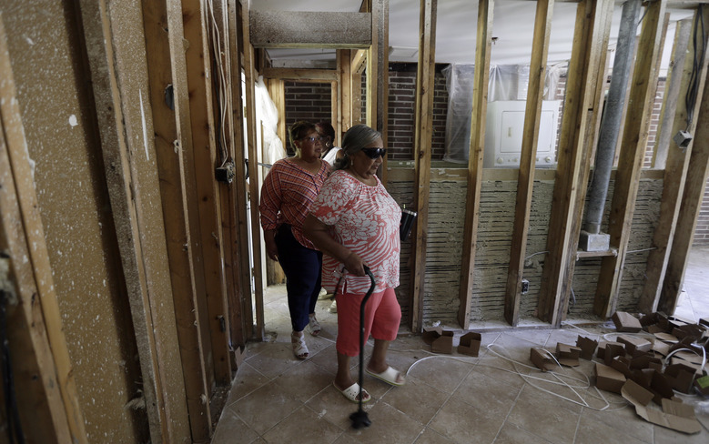In this Tuesday, July 2, 2019, photo, Debora Hudson, left, follows her mother, Carrie Johnson, through Johnson's damaged home as ongoing repairs due to destruction caused by Hurricane Florence continue in Spring Lake, N.C. North Carolina hurricane survivors are frustrated with the slow spending of federal long-term housing recovery funds. (AP Photo/Gerry Broome)