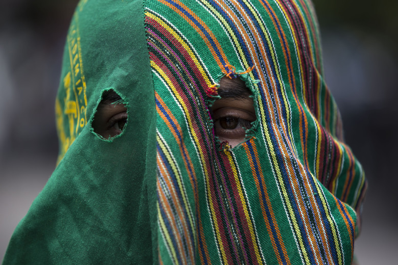 A hooded agronomy student protests outside the hotel where lawmakers are gathered and expected to vote on a deal that Guatemalan President Jimmy Morales' government signed with Washington that would force Salvadoran and Honduran migrants to request asylum in Guatemala instead of the United States, in Guatemala City, Wednesday, July 31, 2019. Critics of the deal point out that Guatemala has the same problems that are driving Hondurans and Salvadorans to flee their homes: violence, poverty, joblessness and a prolonged drought that has severely hurt farmers. (AP Photo/Oliver de Ros)