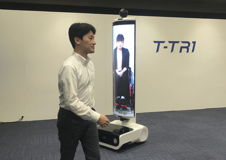 """In this Thursday, July 18, 2019, photo, a T-TRI robot is demonstrated before the media at Toyota Motor Corp. headquarters in Tokyo. The Japanese automaker Toyota, a major Olympic sponsor, is readying various robots for next year's Tokyo Olympics, including the screen-on-wheels designed for """"virtual"""" attendance. The T-TR1 is a moving human-size display designed to represent people who can't be there. (AP Photo/Yuri Kageyama)"""