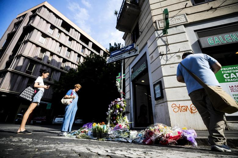 People stop by flowers and messages left on the spot, in Rome, Saturday, July 27, 2019, where Carabinieri officer Mario Cerciello Rega was stabbed to death early Friday. In a statement Saturday, Carabinieri officers investigating the death of Cerciello Rega, 35, said two young American tourists have been detained for alleged murder and attempted extortion. (Angelo Carconi/ANSA via AP)