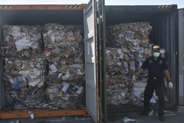 In this Tuesday, July 9, 2019, file photo, custom officers stand near containers of waste at Tanjung Perak port in Surabaya, East Java, Indonesia. Indonesia is sending dozens of containers of imported waste back to Western nations after finding it was contaminated with used diapers, plastic and other materials, adding to a growing backlash in Southeast Asia against being a dumping ground for the developed world's rubbish. (AP Photo)