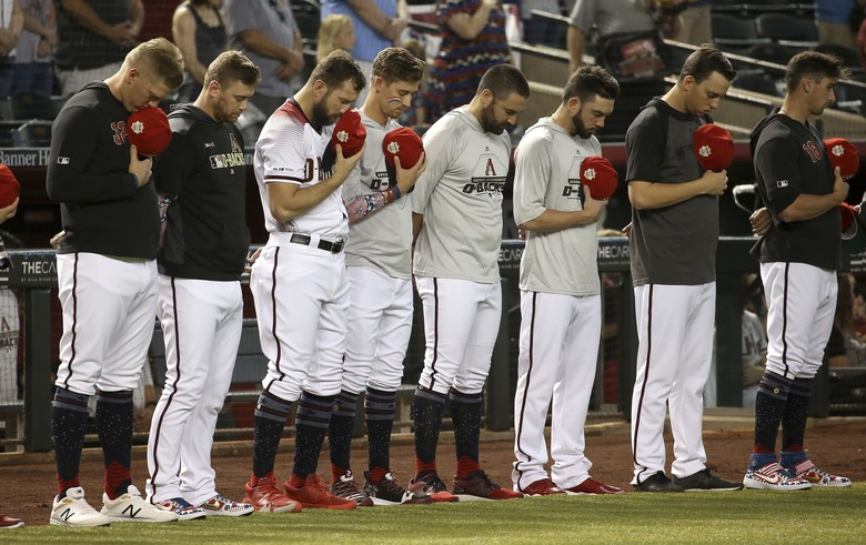 Arizona Diamondbacks players pause during a moment of silence for Los Angeles Angels pitcher Tyler Skaggs prior to a baseball game against the Colorado Rockies, Friday, July 5, 2019, in Phoenix. Skaggs, a former Diamondbacks player, unexpectedly passed away earlier in the week while on a road trip with the Angels in Texas. (AP Photo/Ross D. Franklin)