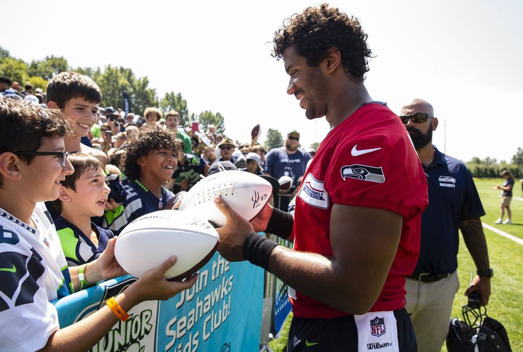 Quarterback Russell Wilson signs autographs during Seattle Seahawks training camp in Renton on Monday. (Erika Schultz / The Seattle Times)