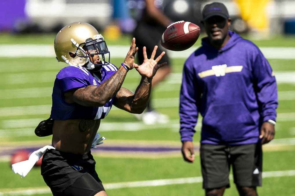 Huskies wide receiver Chico McClatcher makes a catch in front of Junior Adams, wide receivers coach, as the University of Washington holds day five of football training camp at Husky Stadium Tuesday August 6, 2019. (Bettina Hansen / The Seattle Times)