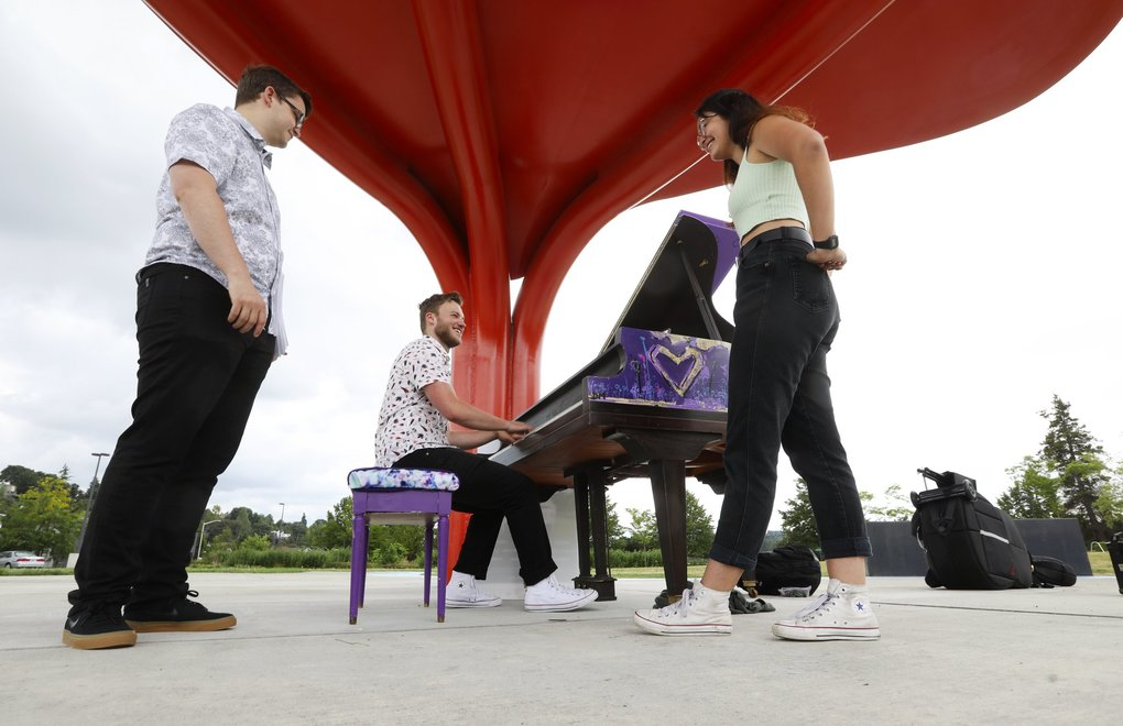 "Musician friends, from left, Dylan Hayes, Ben Feldman and Maia Nelson, who had just finished playing jazz/funk music together in the Ben Feldman Trio, relax around a piano they used in their performance, which was decorated by artist Delton Mosby at Jimi Hendrix Park in Seattle's Central District on Sunday. The piano is one of 13 throughout the area as part of the ""Pianos in the Parks"" event, which runs through August 18. To find them go to www.pianosintheparks.org/   (Ken Lambert / The Seattle Times)"