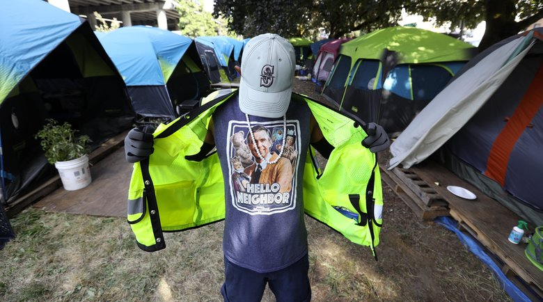 Michael Cleveland, who lives at Tent City 3, shows off his Mister Rogers t-shirt under the vest he wears to work security detail. Cleveland said he relocated to Seattle, where he had heard about Tent City, after losing his home in a fire in California last year.  (Ken Lambert / The Seattle Times)