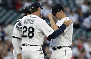 Seattle Mariners relief pitcher Tommy Milone, right, talks with pitching coach Paul Davis (28) and catcher Omar Narvaez after giving up a two-run home run to New York Yankees' Mike Ford in the second inning of a baseball game Monday, Aug. 26, 2019, in Seattle. (AP Photo/Elaine Thompson) WAET105 WAET105