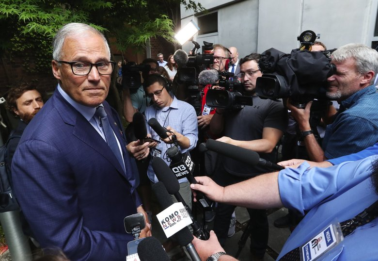 Gov. Jay Inslee, who dropped his presidential bid on Thursday, talks to a crush of media in Seattle after a Title X press conference about running for reelection. He said if he won he would serve his full term. (Ken Lambert / The Seattle Times)