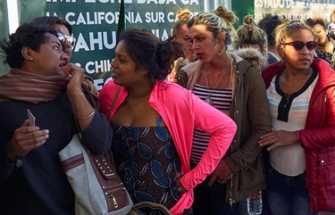 Dozens of transgender women and gay men traveling with the Central American migrant caravan wait in line to receive a number as part of the process to apply for asylum in the United States, at the border in Tijuana, Mexico, Thursday, Nov. 15, 2018. Arriving ahead of the bulk of the Central American migrant caravan, dozens of transgender women and gay men added their names to a book and were given numbers Thursday, with the hope of requesting asylum in the U.S. (AP Photo/Gregory Bull)