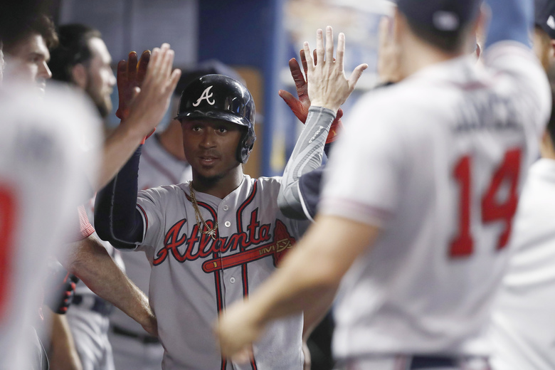 Atlanta Braves' Ozzie Albies is congratulated for his home run during the first inning of the team's baseball game against the Miami Marlins on Friday, Aug. 9, 2019, in Miami. (AP Photo/Brynn Anderson)