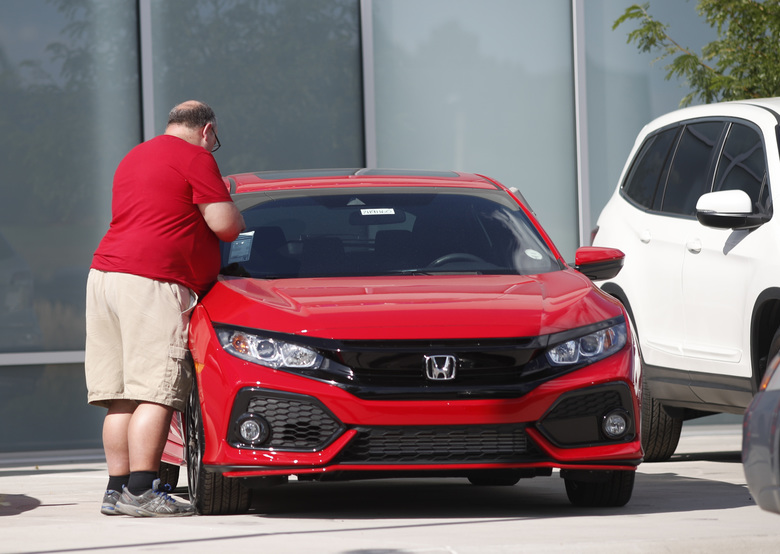 In this Aug. 25, 2019, photograph, a prospective buyer checks over an unsold 2019 Civic sedan outside a Honda dealership in Highlands Ranch, Colo. On Friday, Aug. 30, the Commerce Department issues its July report on consumer spending, which accounts for roughly 70 percent of U.S. economic activity. (AP Photo/David Zalubowski)