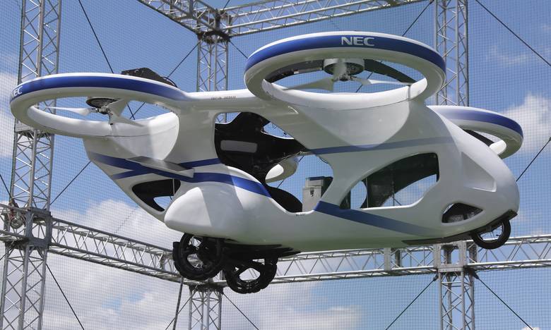 "NEC Corp.'s machine with propellers hovers at the company's facility in Abiko near Tokyo, Monday, Aug. 5, 2019. The Japanese electronics maker showed a ""flying car,"" a large drone-like machine with four propellers that hovered steadily for about a minute. (AP Photo/Koji Sasahara)"
