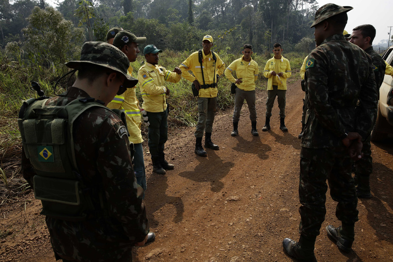 Army soldiers and firefighters prepare to deploy to put out fires in the Vila Nova Samuel region, along the road to the National Forest of Jacunda, near to the city of Porto Velho, Rondonia state, part of Brazil's Amazon, Sunday, Aug. 25, 2019. Leaders of the Group of Seven nations said Sunday they were preparing to help Brazil fight the fires burning across the Amazon rainforest and repair the damage even as tens of thousands of soldiers were being deployed to fight the blazes that have caused global alarm. (AP Photo/Eraldo Peres)