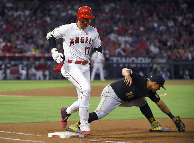 Los Angeles Angels' Shohei Ohtani, left, is safe at first as Pittsburgh Pirates third baseman Jose Osuna takes a late throw during the inning of a baseball game Tuesday, Aug. 13, 2019, in Anaheim, Calif. (AP Photo/Mark J. Terrill)