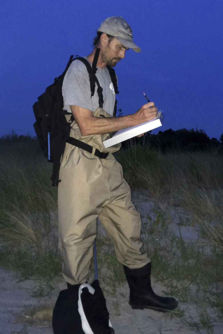 –PLEASE HOLD– This Tuesday, July 16, 2019, photo shows Jason Davis, a biologist with the Delaware Department of Natural Resources and Environmental Control, taking notes on the conditions at a state park near Bethany Beach, Del., before surveying the area in search of the Bethany Beach Firefly, which some environmentalists want added to the federal Endangered Species List. (AP Photo/Randall Chase)