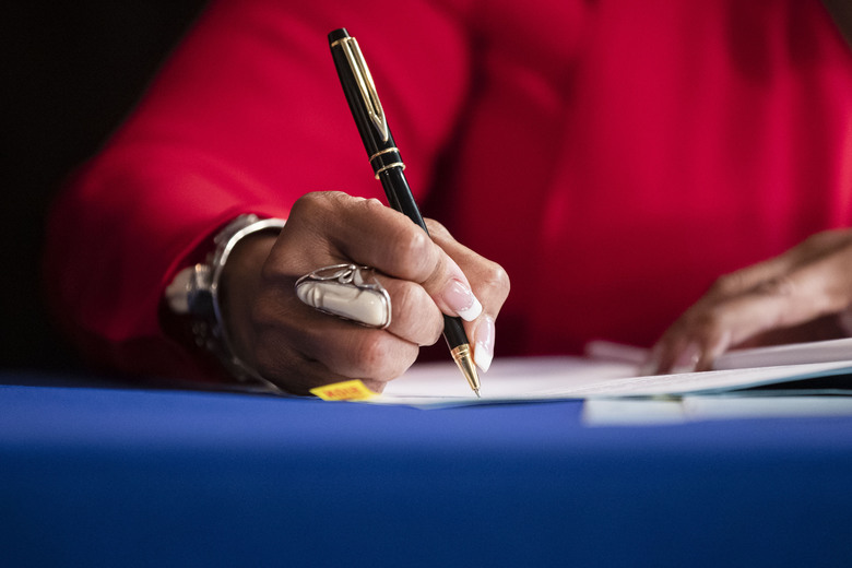 Lt. Gov. Sheila Oliver signs a bill at the state capital in Trenton, N.J., Monday, Aug. 5, 2019. New Jersey has enacted three laws designed to help victims of gun violence avoid becoming hurt again by firearms or seeking out retaliation. (AP Photo/Matt Rourke)