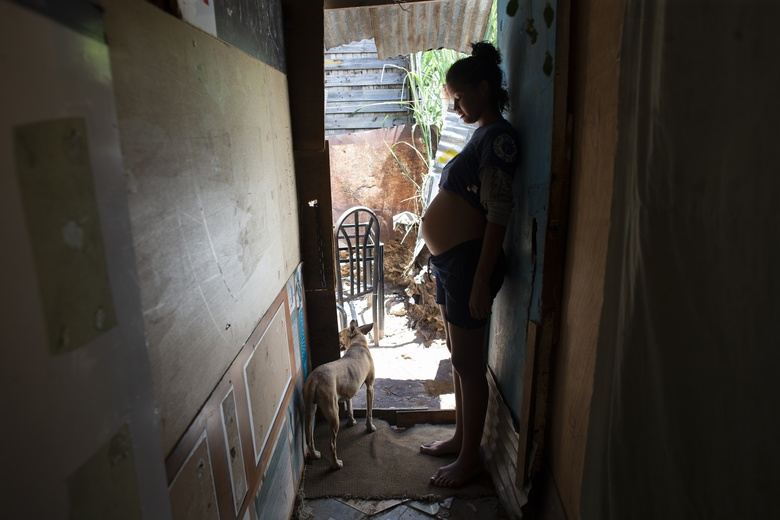 In this photo taken Aug. 5, 2019, 14-year-old Rosibeth Vargas, who is seven months pregnant, stands inside her home where she lives with her parents, 18-year-old sister and nephew, in the Tablitas area of the Caucaguita neighborhood on the outskirts of Caracas, Venezuela. Vargas said her school allows student mothers to bring their children to class, but that she dropped out after being bullied. (AP Photo/Ariana Cubillos)