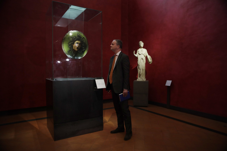"""German director of the Uffizi Galleries, Eike Schmidt, admires Michelangelo Merisi da Caravaggio's 1597 painting  """"Medusa"""" in a glass case, at the Uffizi Gallery museum, in Florence, Italy, Tuesday, Aug. 6, 2019. Under Schmidt's direction, entire rooms were reworked to better show off the works of Italian Renaissance masters Raphael, Michelangelo and Leonardo da Vinci, Schmidt wouldn't have been in position to do any of this without reforms enacted in 2014 by the liberal-leaning government running Italy at the time.  (AP Photo/Luca Bruno)"""