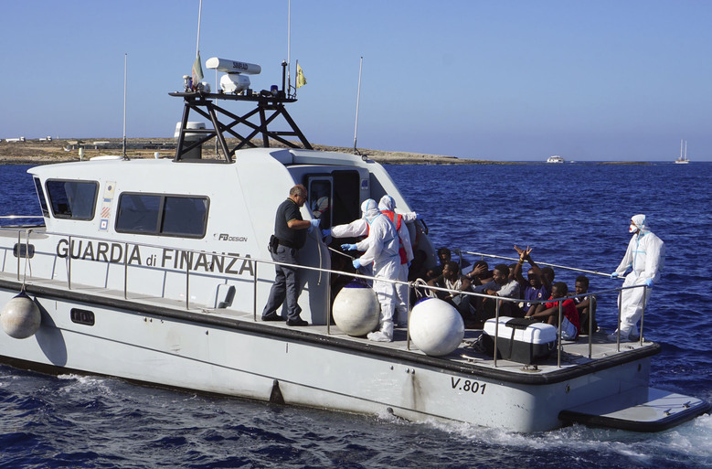 Migrants are evacuated by Italian Coast guards from the Open Arms Spanish humanitarian boat at the coasts of the Sicilian island of Lampedusa, southern Italy, Saturday, Aug.17, 2019. Italy's hard-line interior minister buckled under pressure Saturday and agreed to let 27 unaccompanied minors leave a migrant rescue ship after two weeks at sea, temporarily easing a political standoff that has threatened the viability of the populist government. (AP Photo/Francisco Gentico)