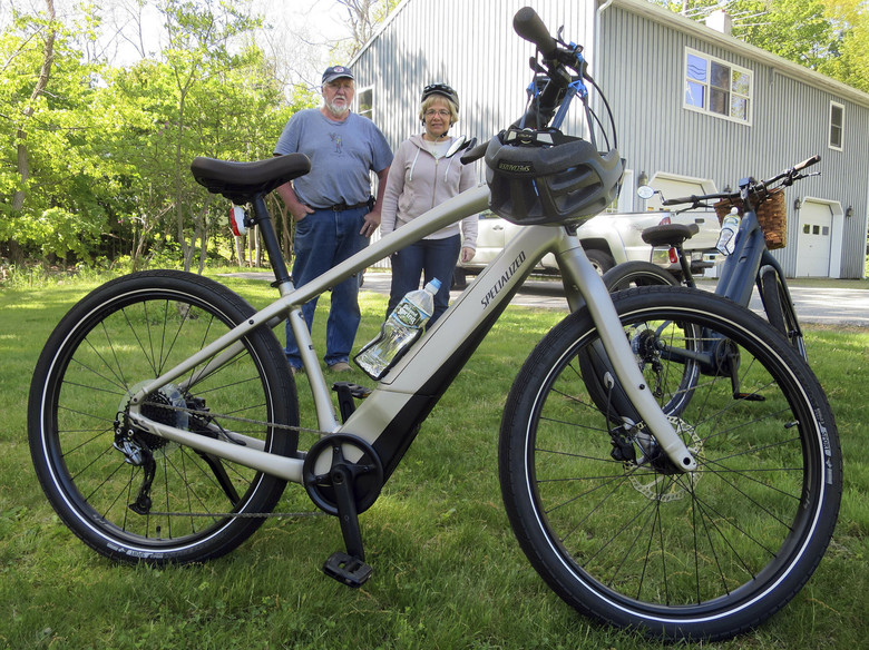 Gordon and Janice Goodwin show their electric-assist bicycles outside their home in Bar Harbor, Maine on June 8, 2019. Motorized electric bicycles may soon be humming their way into serene national parks and other public lands nationwide, under a new Trump administration order allowing the so-called e-bikes on every federal trail where a regular bike can go. (AP Photo/David Sharp, files)