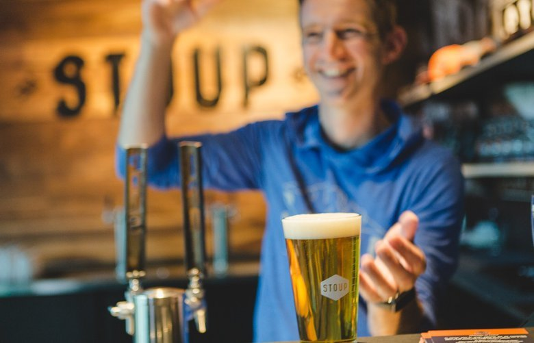Stoup tap room manager Adam Lazowska pours a glass of the brewing company's Pilsner.