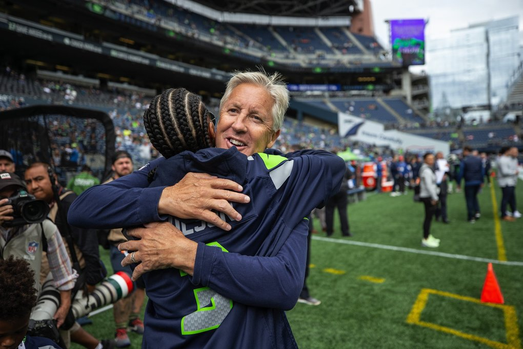 Pete Carroll has a hug for Ciara before Sunday's game. (Dean Rutz / The Seattle Times)