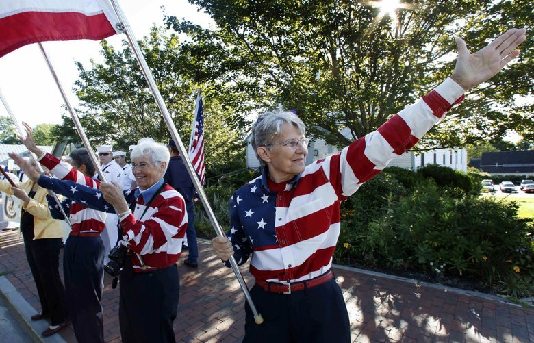 FILE – In this Aug. 23, 2011, file photo, the Freeport Flag Ladies, Carmen Footer, from left, JoAnn Miller and Elaine Greene, wave to vehicles in Freeport, Maine. The three women who've been waving the Stars and Stripes each week since the 9/11 attacks are folding up their flags in Freeport, Maine. The tradition started after the terrorist attacks 18 year ago. (AP Photo/Robert F. Bukaty, File) NYHK301 NYHK301