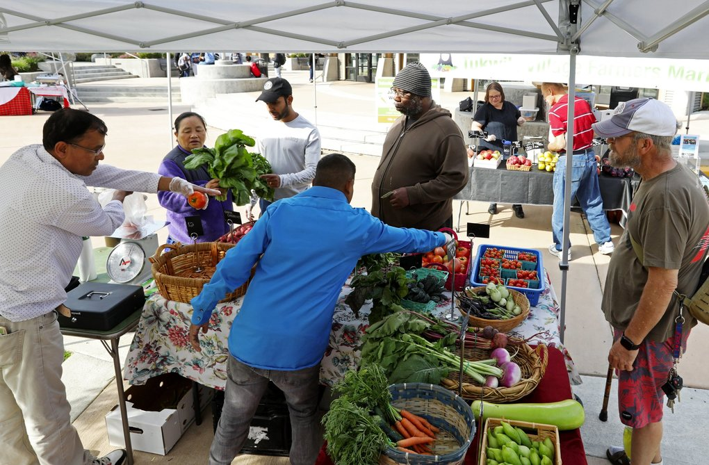 Customers shop for produce at a Tukwila farmers market. The owners of the stand are originally from Bhutan. (Ken Lambert / The Seattle Times)