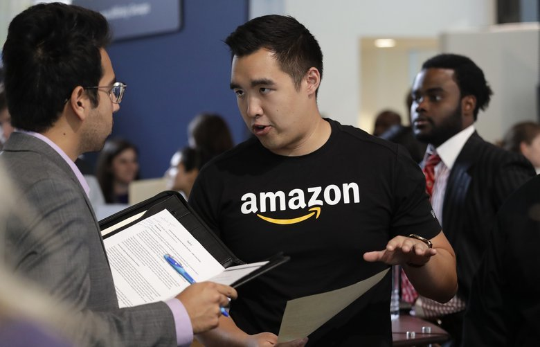 Amazon recruiter Perry Chang speaks with a prospective employee at a job fair hosted by the company Tuesday, Sept. 17, 2019, in Seattle. Amazon is going on a hiring spree. The online shopping giant is holding job fairs across the country, aiming to hire more than 30,000 people by early next year, a 5% bump in its total workforce. (AP Photo/Elaine Thompson) WAET107 WAET107