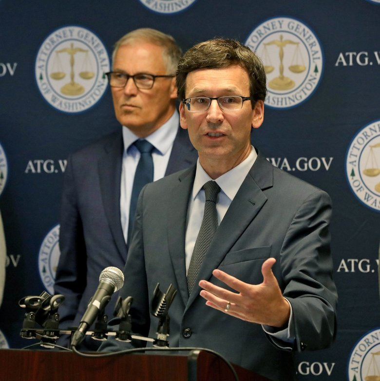 Washington state Attorney General Bob Ferguson, foreground, announces a lawsuit Thursday challenging President Donald Trump's use of military project funding to pay for a wall along the U.S./Mexico border. In the background is Gov. Jay Inslee. (Greg Gilbert / The Seattle Times)