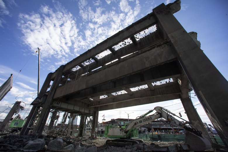 The last portion of the Alaskan Way Viaduct at Marion Street and Alaskan Way, across the street from Colman dock in Seattle, is being demolished at left Thursday.  The last two-tiered section of the old highway could be gone this weekend.  (Ellen M. Banner / The Seattle Times)