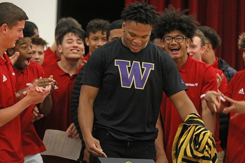 Surrounded by his teammates, Kennedy High School's Sav'ell Smalls announces he's going to the University of Washington. (Greg Gilbert / The Seattle Times)