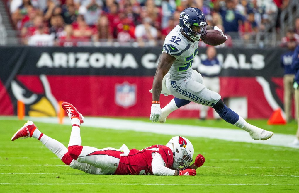 Seattle Seahawks running back Chris Carson (32) flies over an Arizona Cardinals defender on his way to running for 104 yards for the game as the Seattle Seahawks play the Arizona Cardinals at State Farm Stadium in Glendale Arizona on September 29, 2019. (Mike Siegel / The Seattle Times)