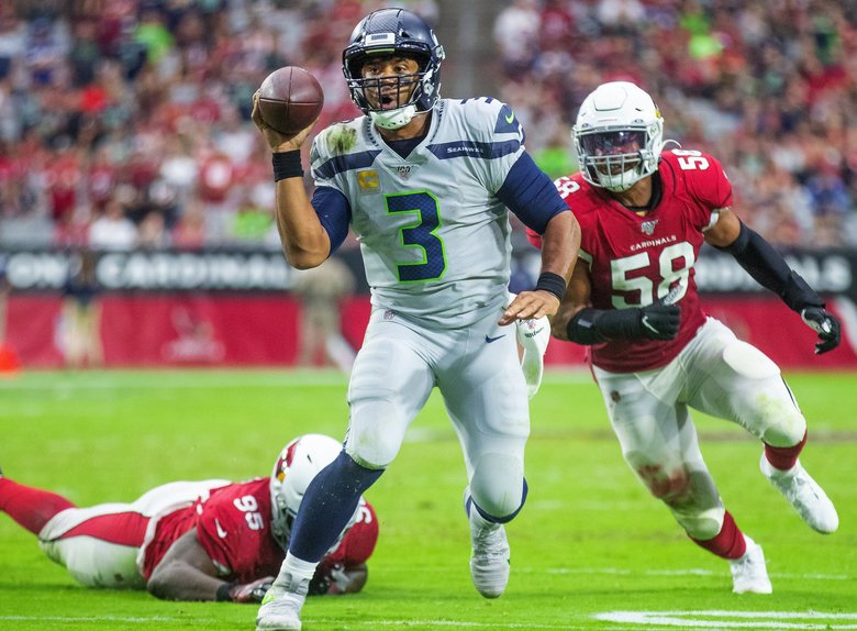Seattle Seahawks quarterback Russell Wilson (3) scrambles out of the pocket, attempts a throw then keeps the ball for a short run during 4th quarter action as the Seattle Seahawks play the Arizona Cardinals at State Farm Stadium in Glendale Arizona on September 29, 2019. (Mike Siegel / The Seattle Times)