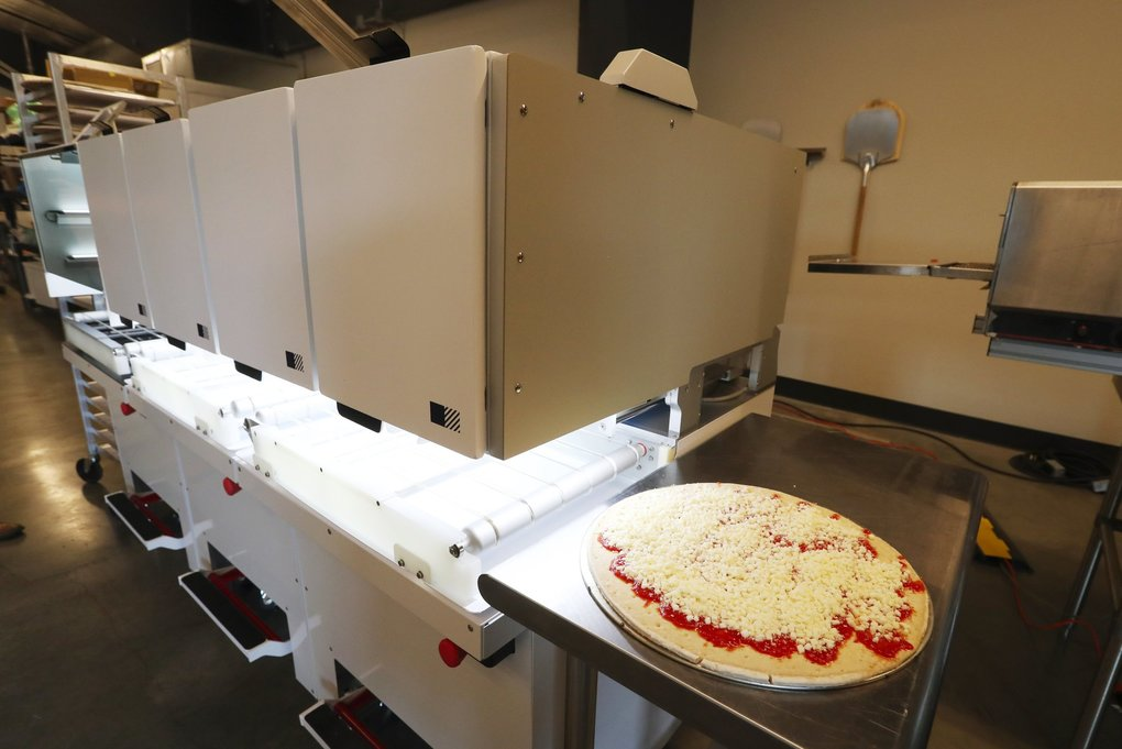 A cheese pizza is ready to for the industrial conveyor oven. (Ken Lambert / The Seattle Times)