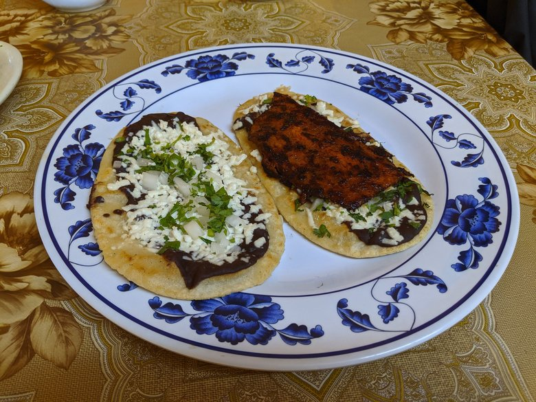 Don't miss the memelas at Taqueria Casa Mixteca. The Oaxacan dish comes with chubby corn tortillas griddled and topped with refried beans, cheese, onion, cilantro and, in this case, pork. (Jackie Varriano / The Seattle Times)