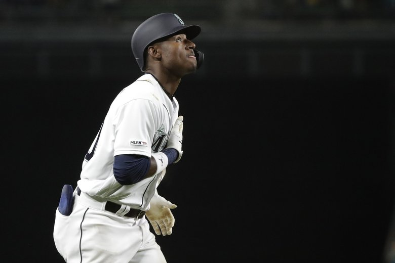 Seattle Mariners' Kyle Lewis puts his hand on his heart and looks up as he heads toward home after hitting a solo home run during the fifth inning of the team's baseball game against the Cincinnati Reds, Tuesday, Sept. 10, 2019, in Seattle, during the second at-bat of his major league debut.  (Ted S. Warren / AP)